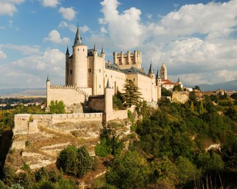 The Alcazar of Segovia is set against a backdrop of mountains